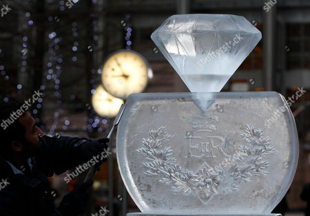 Asanga Amerasinghe an ice sculptor puts the finishing touches to his creation depicting a celebration of Britain's Queen Elizabeth II diamond jubilee year in London, . An sculpting festival takes place in the financial district of London over the upcoming weekend. The Queen will celebrate her diamond jubilee ( 60 years ) since her accession to the throne in 1952
