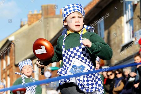 "Harry Bennett aged 6 from the Olney Infant Academy crosses the line to win his section of a children's pancake race in the town centre of Olney, England, . Tradition records that back in 1445, on Shrove Tuesday, the ""Shriving Bell"" rang out to signal the start of the Shriving church service. On hearing the bell a local housewife, who had been busy cooking pancakes in anticipation of the beginning of Lent, ran to the church, frying pan still in hand, still in her apron and a head scarf. The women of Olney recreate this race every Shrove Tuesday by running from the market place to the Church of St. Peter and St. Paul. The winner is the first to cross the line having tossed the pancake a certain number of times"