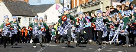 "Stock Picture of Harry Bennett, centre, aged 6, from the Olney Infant Academy looks across at a rival as he goes onto win his section of a children's pancake race in the town centre of Olney, England, . Tradition records that back in 1445, on Shrove Tuesday, the ""Shriving Bell"" rang out to signal the start of the Shriving church service. On hearing the bell a local housewife, who had been busy cooking pancakes in anticipation of the beginning of Lent, ran to the church, frying pan still in hand, still in her apron and a head scarf. The women of Olney recreate this race every Shrove Tuesday by running from the market place to the Church of St. Peter and St. Paul. The winner is the first to cross the line having tossed the pancake a certain number of times"