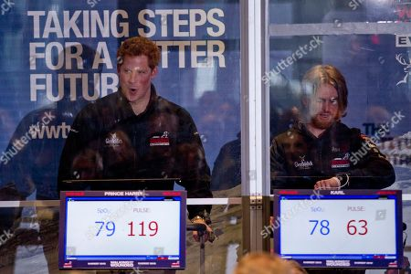 Britain's Prince Harry, left, in his capacity as patron, is seen through a perspex window as he sucks in air whilst walking on a treadmill inside an Altitude Chamber with his increasing pulse rate displayed on a screen below, flanked by expedition member Karl Hinett as they attend the launch event of the Walking With The Wounded Everest 2012 Expedition in London, . The charity, which raises funds to assist with the re-training and re-education of servicemen and women, both veterans and those leaving the Armed Forces, is aiming to have five injured servicemen successfully summit Mount Everest