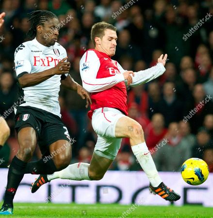 Arsenal's Aaron Ramsey, right, challenges for the ball with Fulham's Dickson Etuhu during their English Premier League during their English Premier League soccer match at the Emirates stadium in London