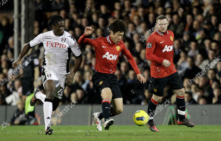 Fulham's Dickson Etuhu, left, competes for the ball with Manchester United's Park Ji-Sung, center, and Wayne Rooney during the English Premier League soccer match between Fulham and Manchester United at Craven Cottage stadium in London