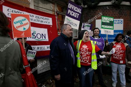 Brendan Barber, center wearing tie, the General Secretary of Britain's Trades Union Congress (TUC) meets striking health workers as he visits a picket line outside St. Pancras Hospital in London, . U.K. border staff joined teachers, hospital workers and weather forecasters Wednesday in Britain's largest strike in decades, but arriving airline passengers appeared to escape the chaos that had been predicted