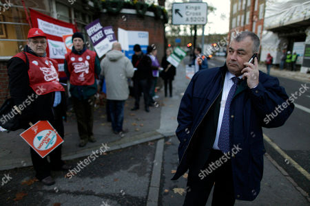 Brendan Barber, the General Secretary of Britain's Trades Union Congress (TUC) speaks on a phone as he visits a picket line outside St. Pancras Hospital in London, . U.K. border staff joined teachers, hospital workers and weather forecasters Wednesday in Britain's largest strike in decades, but arriving airline passengers appeared to escape the chaos that had been predicted