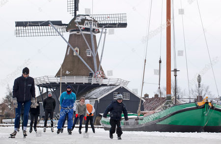 A boy, right, runs alongside skaters who pass a windmill in Woudsend, northern Netherlands. There is nothing more mythical in Dutch sports than an age-old 11-city race skating across lakes and canals in bone-numbing cold from dawn to dusk. No wonder the Netherlands is the greatest speedskating nation in the world. And with Sven Kramer and Ireen Wust leading the way on big oval in Sochi they are bent on proving it again