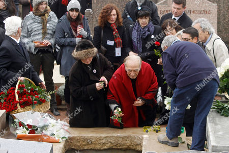 Argentine pianist Miguel Angel Estrella, center, pays homage to former French President Francois Mitterrand's wife Danielle, during her funeral at the Cluny's cemetery, central France, . Mitterrand, a decorated member of the French Resistance and combative advocate for the poor who broke the mold as first lady alongside France's first Socialist president Francois Mitterrand, died Tuesday at age 87