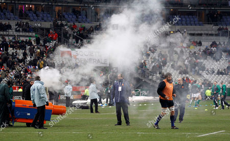 """France's Lionel Nallet, center right, trains as workers use a heating machine before the six nations rugby union match between France and Ireland at the Stade de France stadium, in Saint Denis, outside Paris, . The mach was postponed before kickoff because of freezing weather on Saturday. """"The pitch was unsafe for the players to play,"""" said Ireland coach Declan Kidney, who agreed with the officials' decision"""