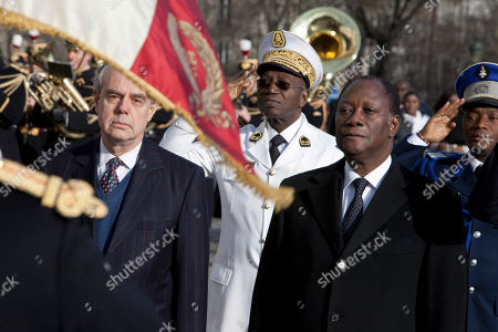 Ivory Coast President Alassane Dramane Ouatarra, right, and French Culture Minister Frederic Mitterand, right, listen the nationals anthems upon their arrival at the unknown soldier's tomb, at the Arc of Triomphe, in Paris, . President Ouattara is on a three day official visit in France