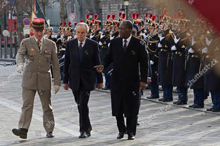 A military official shows the way to Ivory Coast President Alassane Dramane Ouatarra, right, and French Culture Minister Frederic Mitterand, center, prior to the wreath laying ceremony at the unknown soldier's tomb, the Arc of Triomphe, in Paris, . President Ouattara is on a three day official visit in France