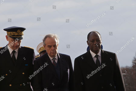 Ivory Coast President Alassane Dramane Ouatarra, right, stands next to French Culture Minister Frederic Mitterand, center, and a military official as he pays respects after laying a wreath at the unknown soldier's tomb, the Arc of Triomphe, in Paris, . President Ouattara is on a three day official visit in France