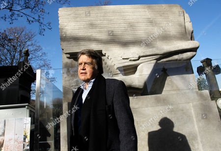 Oscar Wilde's grandson, Merlin Holland poses in front of the newly renovated tombstone of his grand father which coincides with the 111th anniversary of his death, at the Pere Lachaise cemetery, in Paris