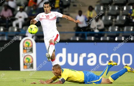 Tunisia's Anis Boussaidi, top, clears the ball as Gabon's captain Daniel Cousin, falls on the ground during their African Cup of Nations Group C soccer match at the Stade de Franceville in Franceville, Gabon
