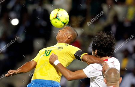 Gabon's captain Daniel Cousin, left, heads the ball as Tunisia's Bilel Ifa, right, defends during their African Cup of Nations Group C soccer match at the Stade de Franceville in Franceville, Gabon