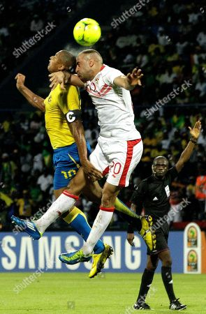 Gabon's Daniel Cousin, top left, and Tunisia's Aymen Abdennour, top center, head the ball as referee Doue Noumandiez Desire of Ivory Coast, right, looks on during their African Cup of Nations Group C soccer match at the Stade de Franceville in Franceville, Gabon, . Gabon beat Tunisia 1-0