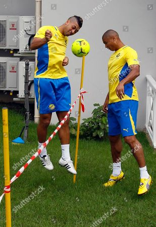 Llyod Palun, Daniel Cousin Gabon Llyod Palun, left, and Daniel Cousin play with a large football type tennis ball, in the courtyard of their hotel in Libreville, Gabon, in preparation for their next African Cup of Nations Group C soccer match against Tunisia in Franceville