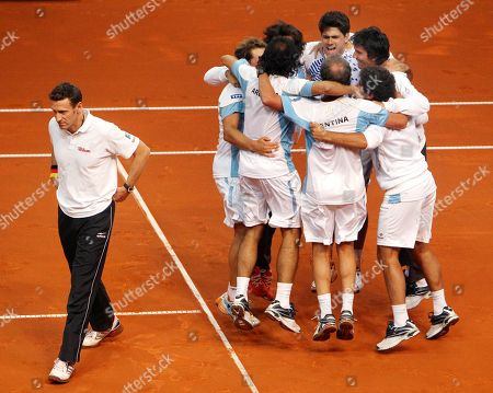 Argentinian players and coaches celebrate after their doubles with David Nalbandian and Eduardo Schwank beat German doubles Philipp Petzschner and Tommy Haas 3-6, 4-6, 6-4, 6-3, 6-4 in a tennis Davis Cup first round match between Germany and Argentina in Bamberg, Germany, Saturday, Feb.11, 2012. Argentina has now a 3-0 lead and goes to the next round. Walking at left is coach of the German team Patrick Kuehnen