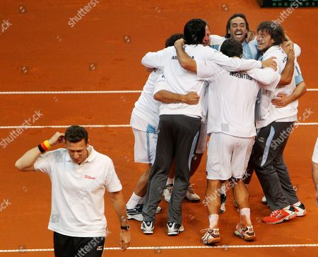 Stock Image of Argentinian players and coaches celebrate after their doubles with David Nalbandian and Eduardo Schwank beat German doubles Philipp Petzschner and Tommy Haas 3-6, 4-6, 6-4, 6-3, 6-4 in a tennis Davis Cup first round match between Germany and Argentina in Bamberg, Germany, Saturday, Feb.11, 2012. Argentina has now a 3-0 lead and goes to the next round. Walking at left is coach of the German team Patrick Kuehnen