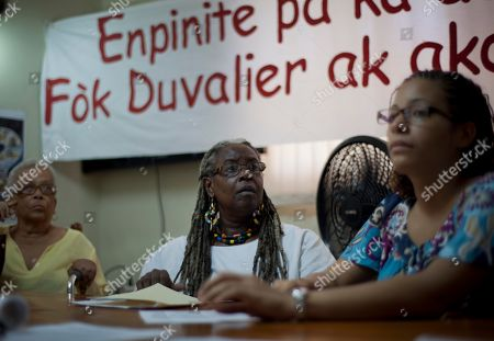 """Danielle Magloire, center, coordinator of Haiti's Collective against Impunity, attends a press conference in Port-au-Prince, Haiti, . The appeals process for parties involved in the high-profile case against former dictator Jean-Claude Duvalier has begun, Haiti's attorney general said Monday. The appeals process comes after a judge recommended that the former strongman knows as """"Baby Doc"""" be tried for alleged financial crimes in a lesser court, and not for the human rights abuses associated with his brutal regime in the 1970s and 1980s. The banner reads in Creole """"Impunity can not be the future of Haiti, Duvalier and his government must go to trial"""