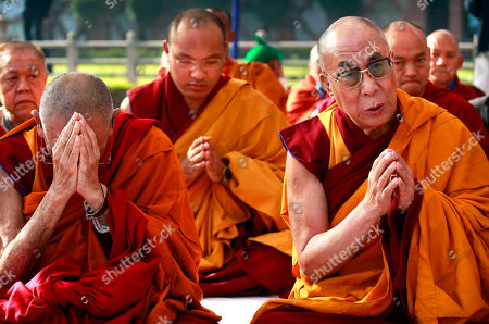 Dalai Lama Tibetan spiritual leader the Dalai Lama, right, and the 17th Karmapa Ogyen Trinley Dorje, center, pray with other Buddhist leaders at an all faith prayer meeting at the Gandhi Memorial in New Delhi, India, . The Dalai Lama is in the Indian capital attending the final session of the Global Buddhist Congregation