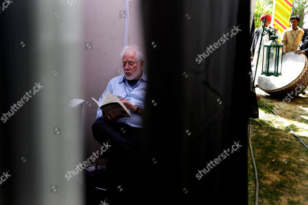 Sri Lankan-born Canadian novelist, poet and Booker Prize-winner Michael Ondaatje reads a book at the back stage green room before presenting his talks at the Jaipur Literature Festival, in Jaipur, in the western Indian state of Rajasthan, . Booker-Prize winning author Salman Rushdie canceled plans to appear at the literature festival Friday after protests from Muslim clerics and warnings that he could be targeted for assassination