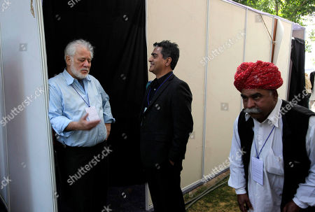 Sri Lankan-born Canadian novelist, poet and Booker Prize-winner Michael Ondaatje, left, talks with Amitava Kumar as an Indian artist walks past during the Jaipur Literature Festival, in Jaipur, in the western Indian state of Rajasthan, . Booker-Prize winning author Salman Rushdie canceled plans to appear at an Indian literature festival Friday after protests from Muslim clerics and warnings that he could be targeted for assassination