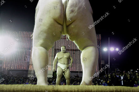 Stock Picture of Kelly Gneiting, three times US champion, back to camera prepares to fight with Byambajav Ulambayar, the reigning World champion during an exhibition Sumo wrestling match in Gauhati, India