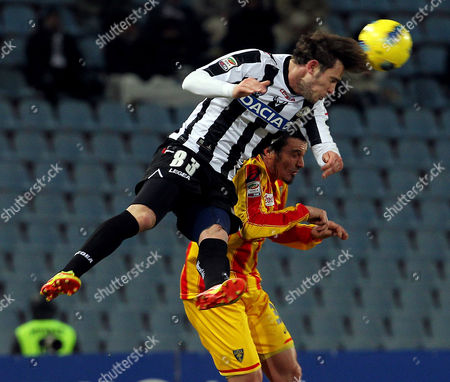 Udinese's Floro Flores, left, and Lecce's Massimo Oddo, jump for the ball during the Serie A soccer match between Udinese and Lecce, at the Udine Friuli stadium, Italy