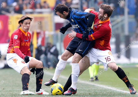 From left, AS Roma midfielder Rodrigo Taddei of Brazil, Inter Milan forward Giampaolo Pazzini and AS Roma striker Daniele De Rossi challenge for the ball during the Serie A soccer match between AS Roma and Inter Milan, in Rome's Olympic stadium