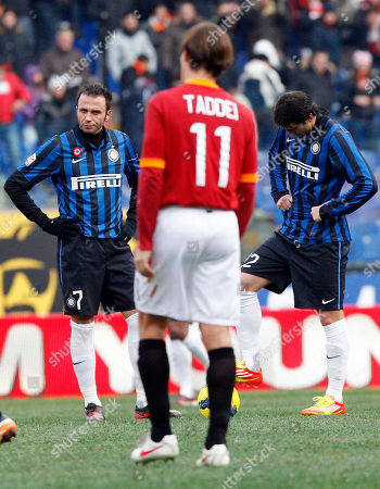 Inter Milan forward Giampaolo Pazzini, left, and Inter Milan Argentine forward Diego Milito, right, react after AS Roma forward Fabio Borini, not seen, scored during the Serie A soccer match between AS Roma and Inter Milan, in Rome's Olympic stadium, . In the center is AS Roma midfielder Rodrigo Taddei of Brazil