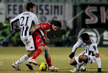 Catania's Marco Biagianti, center, Siena's Andrea Rossi, left, and Simone Vergassola, right, vie for the ball during a Serie A soccer match at the Artemio Franchi stadium in Siena, Italy, . Catania won 1-0