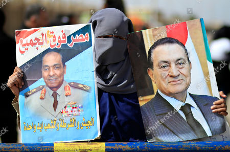 """An Egyptian woman holds posters of Field Marshal Mohamed Hussein Tantawi, head of Egypt's ruling military council, left, and the ousted Egyptian President Mubarak outside a courtroom in Cairo, Egypt, . Egypt's ousted President Hosni Mubarak has turned down the chance to address the court on the last session before the verdict in his seven-month trial. Arabic writing on the poster reads, """"Egypt is above all, the army, the police and, the people, one hand"""