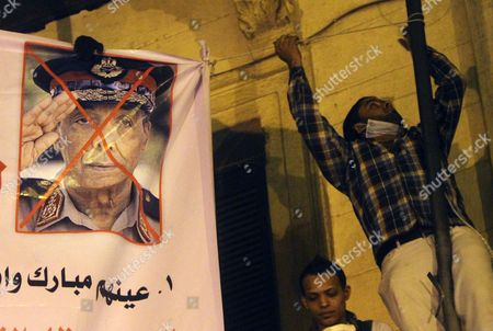 """An Egyptian protester hangs a crossed out poster of Egypt's military ruler, Field Marshal Mohamed Hussein Tantawi, the head of SCAF, The Supreme Council of the Armed Forces, at Tahrir Square in Cairo, Egypt, Tuesday, Nov.22, 2011. Egyptian politicians say the ruling military has moved up the date for transferring power to a civilian government to . Arabic reads """" Mubarak hired them"""