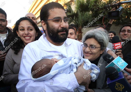Egyptian prominent blogger Alaa Abdel Fattah, left, hugs his recently born son, Khaled, his mother Laila Soueif, and his sister Ahdaf Soueif, left, after after he was released in Cairo, Egypt, . An Egyptian court ordered the release of Alaa after detained nearly two months ago by the ruling military for his alleged role in deadly sectarian clashes in October