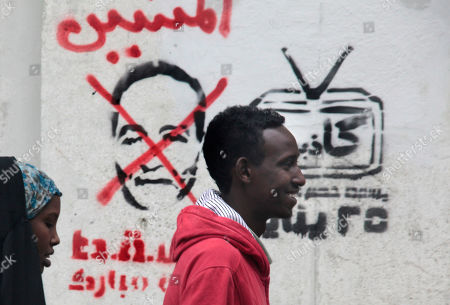 """Egyptians pass by anti-Supreme Council for the Armed Forces (SCAF) graffiti showing Field Marshal Mohamed Hussein Tantawi, the head of Egypt's military ruling council, at Tahrir square in Cairo, Egypt, . Hundreds of Egyptians protested in Tahrir Square Monday demanding that SCAF step down from power. The Arabic writing reads, """"layers"""
