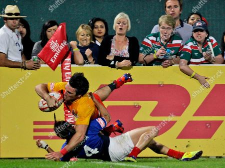 England's Mat Turner dives to score a try over Terry Bouhraoua from France during the final match of Dubai Rugby Sevens Cup, in Dubai, United Arab Emirates