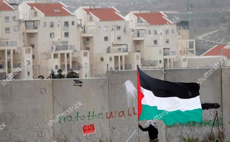 """A protestor waves a Palestinian flag in front of Israeli troops during a protest against Israel's separation barrier in the West Bank village of Bilin, near Ramallah. A film made by Bilin resident and amateur filmmaker Emad Burnat has been shortlisted for an Oscar. The film """"5 Broken Cameras,"""" features footage shot by Burnat, who bought a camera to film home videos but ended up documenting six years of family life on the backdrop of weekly Palestinian demonstrations against the building of Israel's separation barrier through Bilin. Two Israeli-produced documentaries about the conflict have been shortlisted for nomination in this year's Academy Awards"""