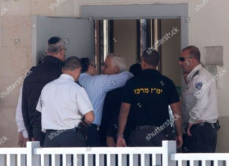 """Former Israeli President Moshe Katsav, center right, hugs his son as he enters prison to begin a seven-year sentence, in the central Israeli town of Ramla, . Katsav entered a minimum security prison on Wednesday to start serving a seven-year sentence for rape, but not before defiantly accusing the state of Israel of """"executing"""" an innocent man"""