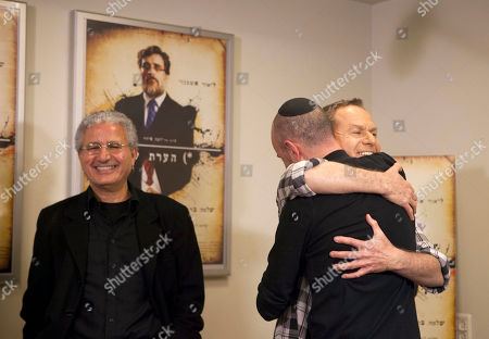 """Israeli film directed Joseph Cedar and actor Shlomo Bar Aba hug during a press conference after the film """"Footnote"""", a mordant tale of rivalry between father-son Talmudic scholars was nominated in the Academy Awards' best foreign-language film category, in Tel Aviv, Israel, . Cedar, who was Oscar nominated in 2008 for """"Beaufort,"""" said it was """"very flattering"""" to be nominated in what he called """"a great year for foreign film at the Oscar."""" Producer Moshe Edry is at left"""