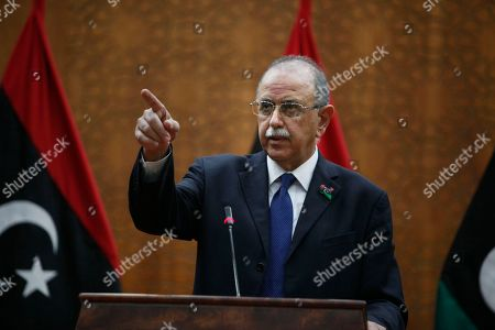 Libya's interim prime minister Abdurrahim el-Keib talks as he announces the formation of a transitional government that will lead the oil-rich country, in Tripoli, Libya, Tuesday, Nov.22, 2011