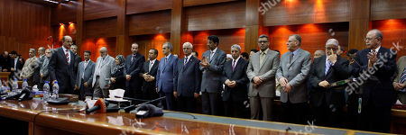 """The new transitional cabinet ministers stand during a press conference in Tripoli, Libya, . Libya's transitional government was sworn in Thursday before the country's interim leader, another step in the oil-rich country's roadmap to elections next year. Starting with Prime Minister Prime Minister Abdurrahim el-Keib, each minister faced the transitional council's leader, Mustafa Abdel-Jalil, placed his hand on a Quran and swore to """"remain loyal to the goals"""" of the revolution that overthrew longtime leader Moammar Gadhafi"""