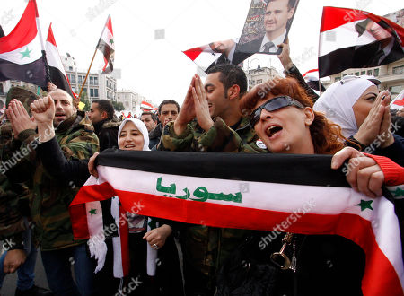 "Stock Image of Syrian soldiers and others chant slogans and hold a scarf in the colors of the Syrian national flag and the word, ""Syria,"" in Arabic, during a pro-regime rally in Damascus, Syria, . The rebel Free Syrian Army said Friday it has stopped its offensive against government targets during a month-long mission by Arab Legue monitors, saying it wants to expose how the regime is killing peaceful protesters"