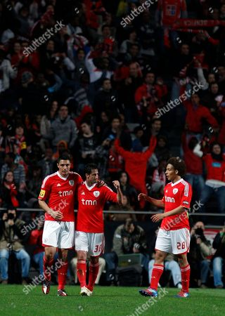 Benfica's Oscar Cardozo, left, from Paraguay, celebrates with teammates Joan Capdevila, center, from Spain, and Axel Witsel, from Belgium, after scoring their team's victory goal during their Portuguese League Cup semifinal soccer match against Porto at Benfica's Luz stadium in Lisbon, . Benfica won 3-2 and will play the final