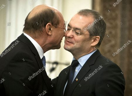 Romania's President Traian Basescu, left, kisses outgoing Premier Emil Boc, right, after the swearing in ceremony of a new government in Bucharest, Romania, . Romania's Parliament has approved the government of foreign espionage chief Mihai Razvan Ungureanu, which the ruling coalition hopes will improve its popularity ahead of parliamentary elections this year. Lawmakers voted 237-2 on Thursday for Ungureanu's Cabinet, which needed 232 votes to take office. The opposition boycotted the vote