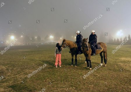 A girl, fan of Bosnian pop singer Dino Merlin's, speaks with Serbian police officers on horses, near Belgrade Arena, before Merlin's concert, in Belgrade, Serbia, Friday, Nov.25, 2011. This is the first concert in Belgrade after more than 20 years, after breakup of Yugoslavia. Serbian ultra-nationalists called Serbian fans to boycott the event