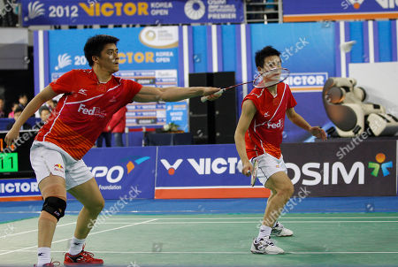 China's Fu Haifeng, left, returns to South Korea's Jung Jae-sung and Lee Yong-dae as his teammate Cai Yun, right, looks on in men's doubles final match at the Korea Open Badminton Super Series Premier in Seoul, South Korea, . China defeated South Korea 2-1