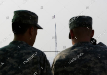Stock Image of U.S. Army soldiers look at a North Korean flag, flying at North Korea's Tae Sung Dong, in Paju near Panmunjom inside the Demilitarized Zone separating South and North Korea . North Korea commemorated Kim Jong Il's 70th birthday Thursday with the flowers that bear his name, a military parade and pledges of loyalty to the son who has taken his place