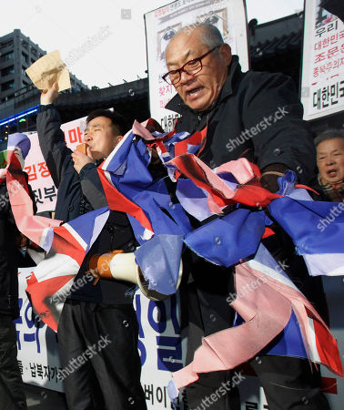 An anti-North Korean protester tears up a North Korea flag during a rally to oppose visit by South Korean civilians and private organizations to North Korea to make a call of condolence for deceased North Korean leader Kim Jong Il, in front of Deoksu Palace in Seoul, South Korea, . Lee Hee-ho, widow of late former South Korean President Kim Dae-jung, and Hyundai Group Chairwoman Hyun Jeong-eun are part of a 18 person group allowed by South Korea to attend the Dec. 28 funeral of late North Korean leader Kim Jong Il in Pyongyang, North Korea