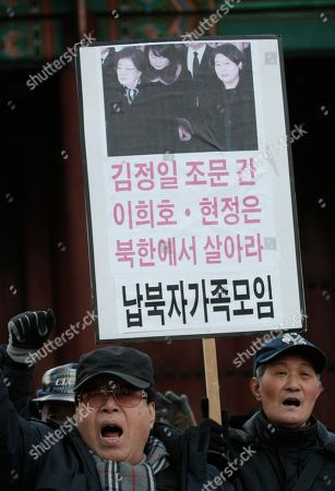 """Anti-North Korean protesters with a picture showing Lee Hee-ho, left, widow of late former South Korean President Kim Dae-jung, and Hyundai Group chairwoman Hyun Jeong-eun shout slogan during a rally to oppose South Korean civilians and private organizations visiting North Korea for late North Korean leader Kim Jong Il, in front of Deoksu Palace in Seoul, South Korea, . Lee and Hyun are part of a 18 person group allowed by South Korea to attend the Dec. 28 funeral for Kim Jong Il in Pyongyang, North Korea. The letters read """"Lee Hee-ho and Hyun Jeong-eun live in North Korea"""