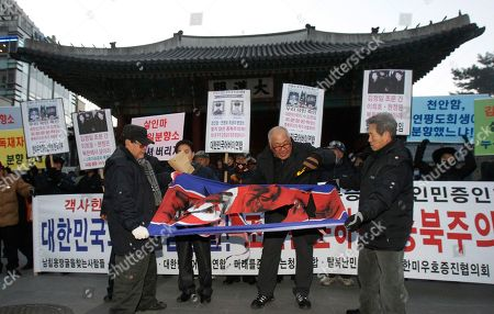 """An anti-North Korean protester with a knife tears a North Korea flag during a rally to oppose that South Korean civilians and private organizations visit North Korea for condolence for late North Korean leader Kim Jong Il, in front of Deoksu Palace in Seoul, South Korea, . Lee Hee-ho, widow of late former South Korean President Kim Dae-jung, and Hyundai Group chairwoman Hyun Jeong-eun are part of a 18-person group allowed by South Korea to attend the Dec. 28 funeral for Kim Jong Il in Pyongyang, North Korea. The letters on a banner read """" Oppose civilians and private organizations visiting North Korea to make a call of condolence for deceased North Korean leader Kim Jong Il"""