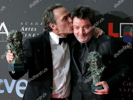 "Jose Coronado, Enrique Urbizu Spanish actor Jose Coronado, left, winner of the best male actor award, kisses Spanish director Enrique Urbizu, winner of the best director award, while they hold their Goya trophies for the film ""No habra paz para los malvados"" at the Goya film awards in Madrid, Spain"